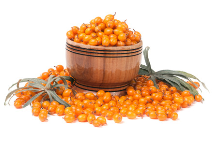 Sea-buckthorn berries in a wooden bowl with leaves isolated on white background.