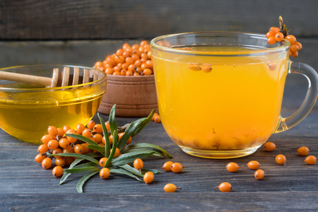 argousier: Tea of sea-buckthorn berries with honey and a branch on a wooden background. Banque d'images