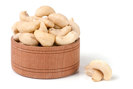 cashew nuts in a wooden bowl isolated on white background.