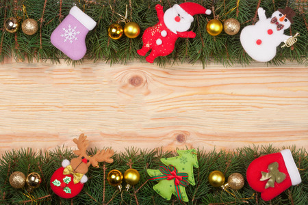 Christmas frame made of fir branches decorated with golden balls Snowman and Santa Claus on a light wooden background.