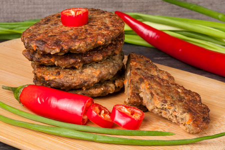 green onions: liver pancakes or cutlets with chili pepper and green onions on a wooden background. Stock Photo