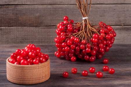 viburnum berries in a bowl on a wooden background.