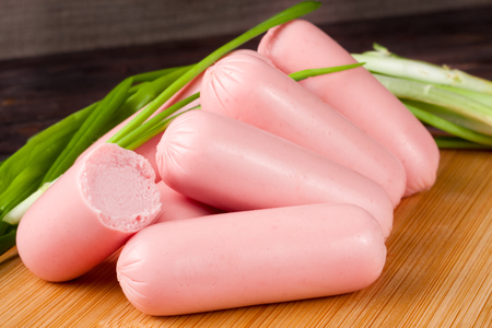 heap of Sausage with green onion on a wooden background. Stock Photo
