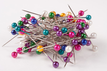 pile of of multi-colored sewing pins on a white background. Stock Photo
