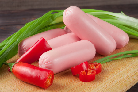 heap of sausages with spring onion and chilli on a cutting board   wooden background