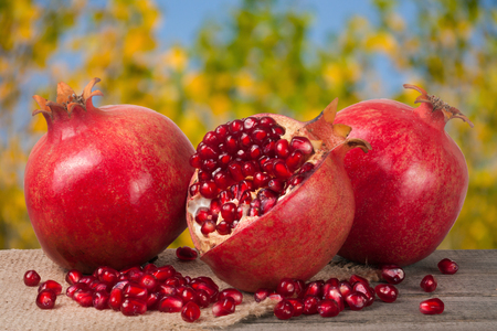 two and a half: two whole pomegranate and half on the old wooden board with blurred garden background