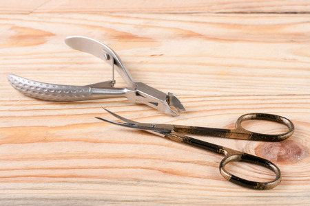 nail scissors and clippers to remove the cuticle care products on a light wooden background