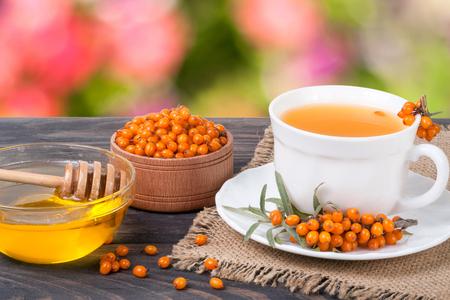 Tea of sea-buckthorn berries with honey on wooden table blurred garden background Stock Photo