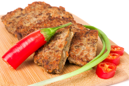 liver pancakes or cutlets with chilli and spring onions on a cutting board close-up isolated white background