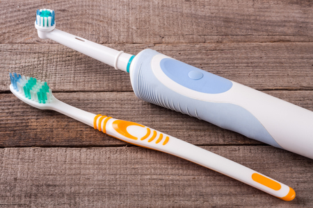 electric and manual toothbrushes on the wooden background