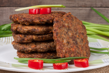 liver pancakes or cutlets with chili pepper and green onions on a wooden background Stock Photo