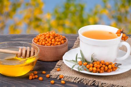 Tea of sea-buckthorn berries with honey on wooden table blurred garden background Imagens