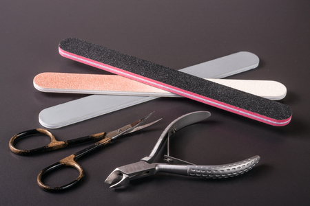 nail scissors file and clippers to remove the cuticle care products on a dark background Stock Photo
