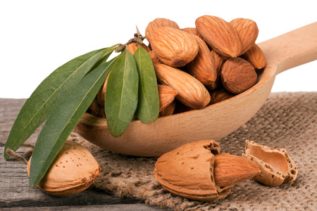 heap of peeled almonds with leaf in a wooden spoon on table isolated  white background Stock Photo