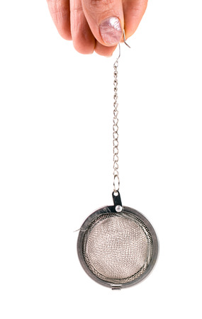 infuser: tea strainer on a chain in  hand isolated  white background