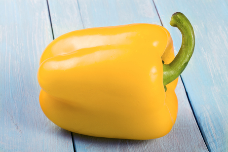yellow sweet pepper on blue wooden background
