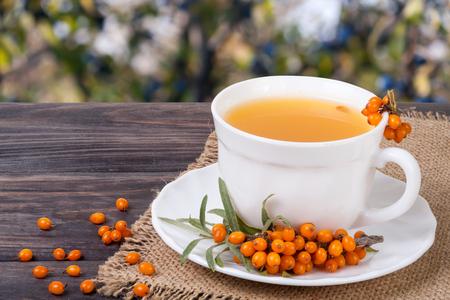 argousier: Tea of sea-buckthorn berries with honey on wooden table blurred garden background Banque d'images
