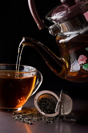 cup of tea with teapot on dark background