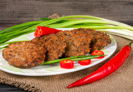 ovine: liver pancakes or cutlets with chili pepper and green onions on a wooden background Stock Photo