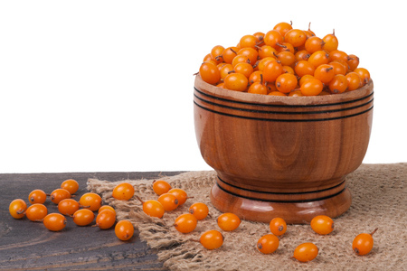 Sea-buckthorn berries in a wooden bowl on table isolated  white background