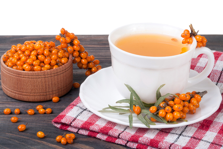 Tea of sea-buckthorn berries on wooden table isolated white background