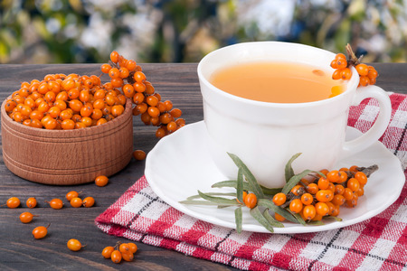 Tea of sea-buckthorn berries on wooden table with blurred garden background
