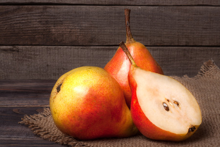 two and a half: two pears with half on a dark wooden background