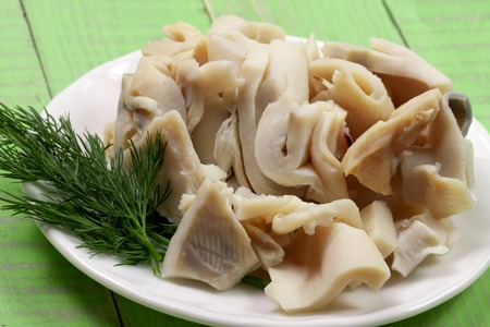 sliced squid on a plate on a green wooden background.