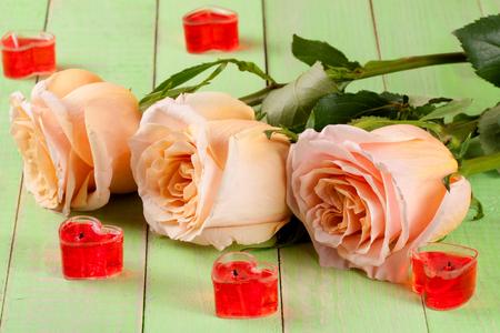 bougie coeur: trois beige rose avec des bougies en forme de coeur sur un fond en bois vert
