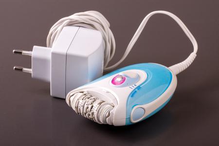 epilator: electric epilator or depilator hair on a dark background