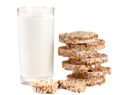 galettes: glass of milk with grain crispbreads isolated on white background Stock Photo