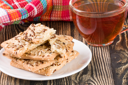 sesame cracker: crispy bread with seeds of sunflower, flax and sesame seeds with a cup of tea on a dark wooden background Stock Photo