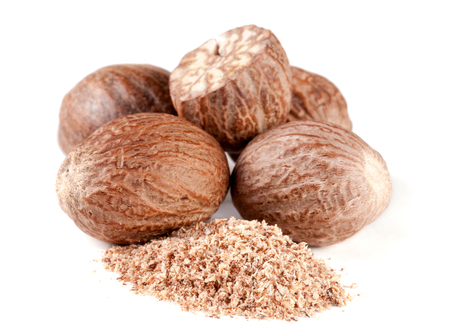 a heap of nutmeg and powder isolated on white background