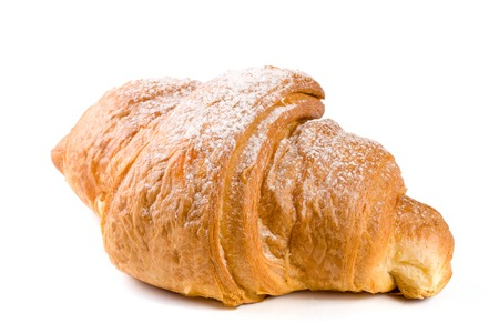 one croissant sprinkled with powdered sugar isolated on a white background closeup Stock Photo