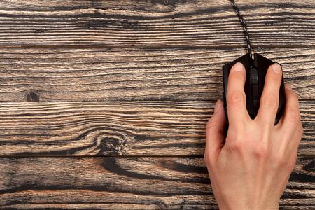 テキストのコピー スペースと黒の木製の背景に手をブラックのコンピュータ ・ マウスです。トップ ビュー