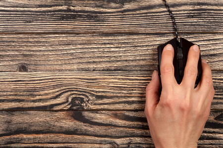 black computer mouse with a hand on a black wooden background with copy space for your text. Top view
