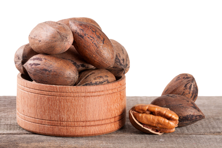 pekan: pecan nuts in a wooden bowl on the old board. Stock Photo