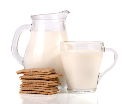 jug and glass of milk with stack of grain crispbreads isolated on white background