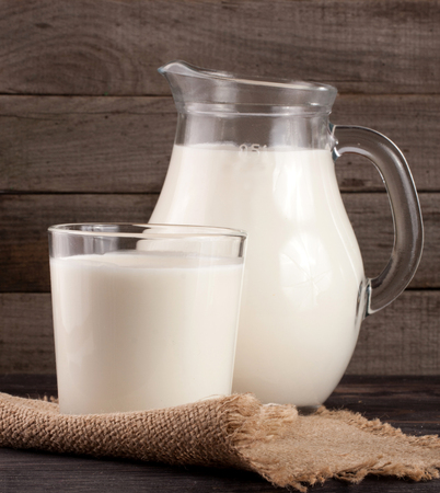 jag: jug and glass of milk on a wooden background