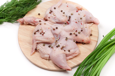 raw chicken carcass with peppercorns and greenery on the cutting board isolated on white background
