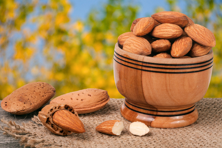 almonds in a bowl on the old wooden board with sackcloth and blurred garden background