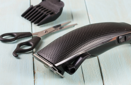 black appliances: hair trimmer with scissors on the wooden background Stock Photo