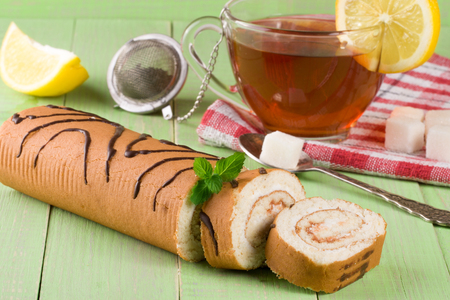 Biscuit swiss roll with a cup of tea on green wooden background