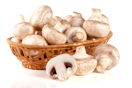 Champignon mushrooms in a wicker basket isolated on white background