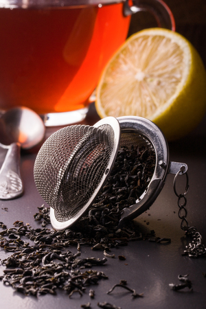 tea strainer with a cup on dark background