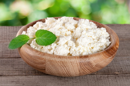 Cottage cheese in a wooden bowl on board with blurred garden background.