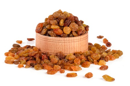 raisins in a wooden bowl isolated on white background. Selective focus