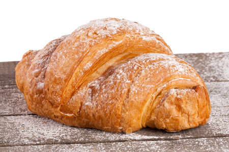 croissant sprinkled with powdered sugar on a wooden table with white background