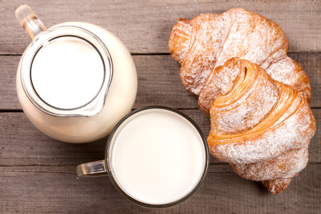 crescent: jug and glass of milk with croissants on a wooden background. Top view.