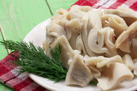 sliced squid on a plate on a green wooden background Stock Photo